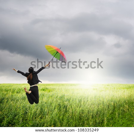 Business woman jumping to raincloud in grassland with rainbow umbrella - stock photo
