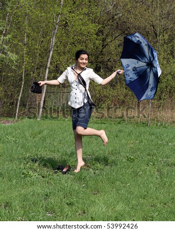 Business woman jumping with umbrella - stock photo