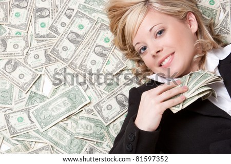 Business woman laying in money - stock photo