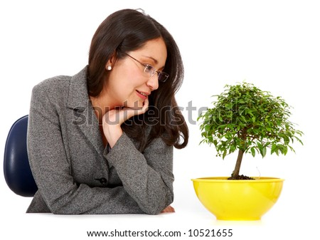 business woman looking after her bonsai tree hoping for fast growth isolated over a white background - stock photo