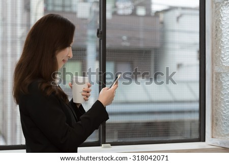 Business woman looking at mobile smartphone