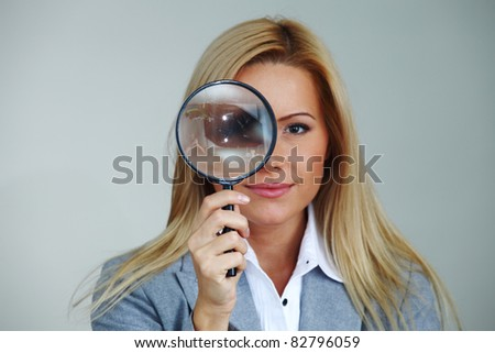 business woman looking through a magnifying glass - stock photo