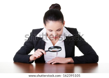 Business woman looking through magnifying glass on table. Isolated on white.  - stock photo