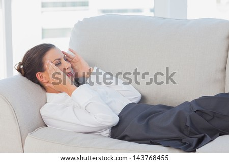 Business woman lying on couch with headache in the office - stock photo