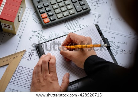 Business woman makes calculations, drawings, diagram, writes the formula on table with blueprints, toy house and calculator.  - stock photo