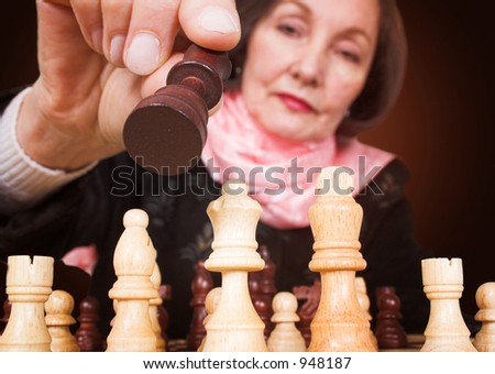 business woman making a move in a chess game - stock photo