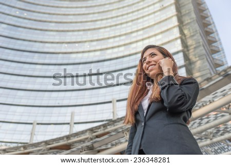 business woman making a phone call outside business center - stock photo