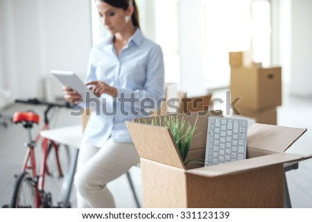 Business woman moving in a new office, she is using a digital tablet, selective focus, open cardboard box on foreground - stock photo