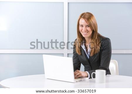 Business Woman on laptop in a modern loft office - stock photo