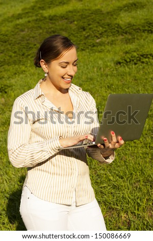 Business woman on street with a laptop typing - stock photo