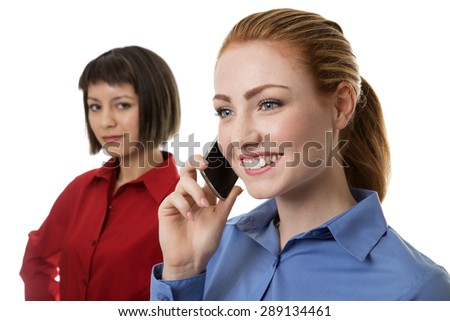 business woman on the phone in the foreground with a woman standing behind her - stock photo