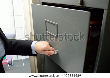 Business woman opening an old file cabinet in the office - stock photo
