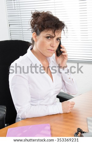 Business woman phoning in office, sitting at an office desk with one hand holding the phone, and in another folder.