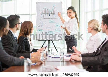 Business woman pointing at a growing chart during a meeting, - stock photo
