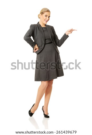 Business woman pointing at copyspace on the left. - stock photo