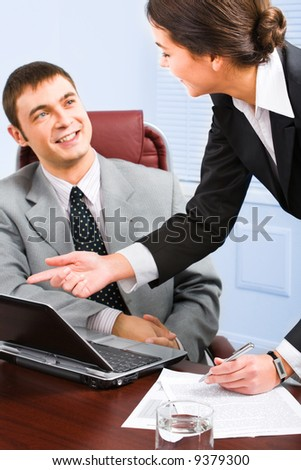 Business woman pointing at laptop and speaking with her colleague