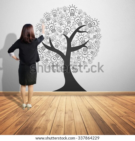 Business woman pointing  concept picture of idea tree on wood  floor and Concrete wall background - stock photo