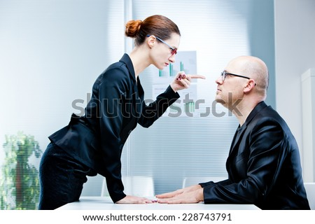 business woman pointing out a business man reproaching him at work in an office - stock photo