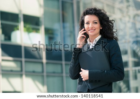 Business woman portrait outdoors talking at the phone with modern building as background. - stock photo
