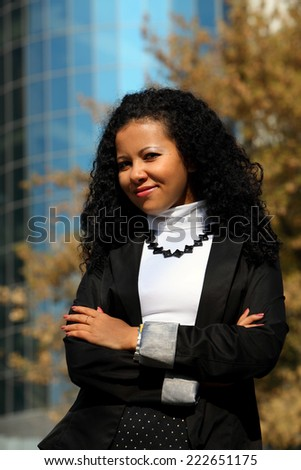 Business woman portrait outdoors, with modern building as background