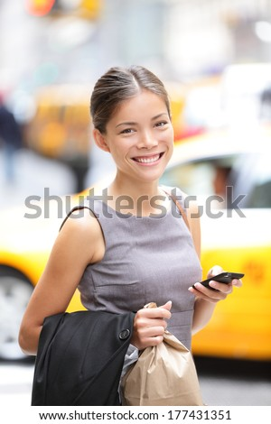 Business woman portrait with smart phone in New York City, Manhattan walking in dress suit holding doggy bag smiling. Young multiracial Asian Caucasian professional female businesswoman in her 20s. - stock photo