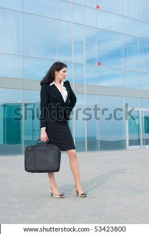 Business woman posing with a laptop's bag in a front of modern office building - stock photo