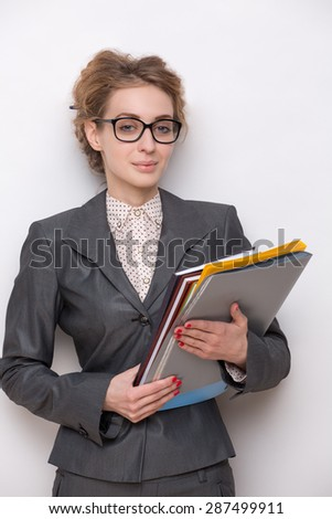 Business woman posing with documents in photosudio. Woman dressed in grey business suit with upswept hair of red colour.