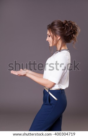 Business woman presenting a copyspace. Grey background. Hairstyle - stock photo