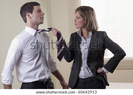 Business woman pulling his colleague from necktie - stock photo