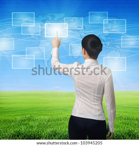 business woman pushing virtual icons in interface over green grass and blue sky landscape - stock photo