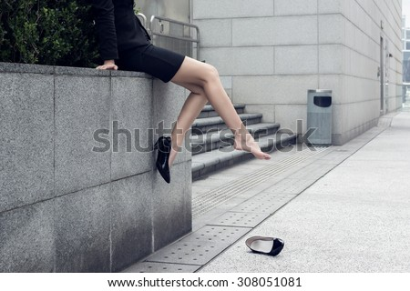 Business woman put a high-heeled shoe on the ground. Concept of wait, rest or induce.