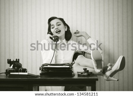 Business woman puts her feet up on her desk on the phone - stock photo
