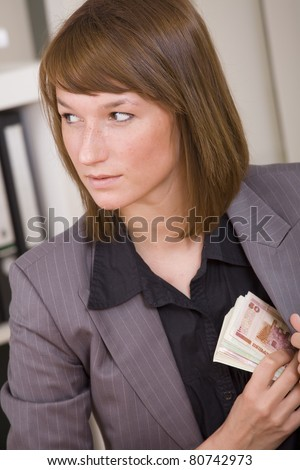 Business woman putting cash to her suit pocket - bribe scene - stock photo