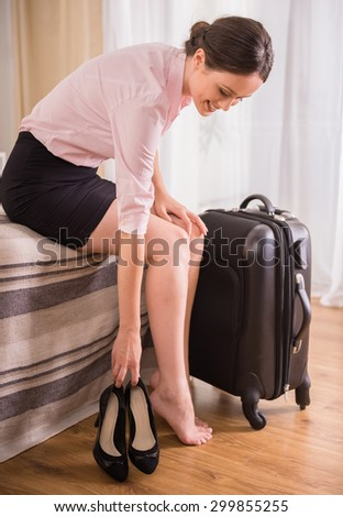 Business woman putting down her shoes while sitting on bed near suitcase at the hotel room. - stock photo