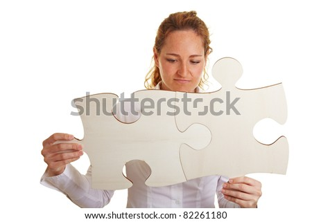 Business woman putting together two oversized jigsaw pieces - stock photo