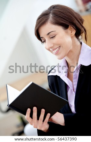 Business woman reading a book at the office