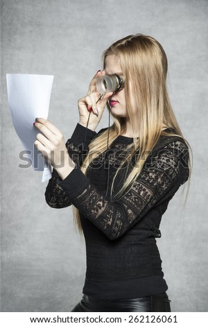 business woman reading a contract with the magnifying glass - stock photo