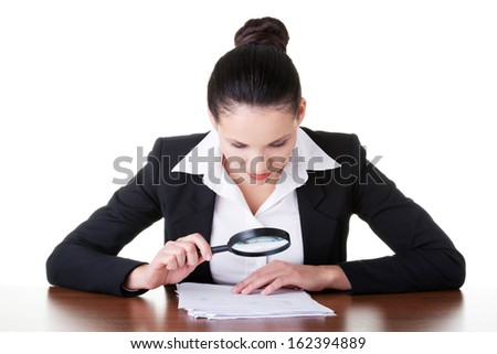 Business woman reading though magifying glass. Isolated on white.  - stock photo
