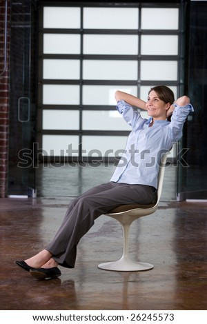 Business woman relaxing in a chair at a modern office
