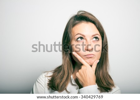 Business woman remembers or thought. office manager. studio photo on a gray background - stock photo