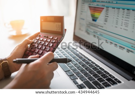 Business woman review company invoice on his desk made a payment. laptop computer, pen and calculator. - stock photo