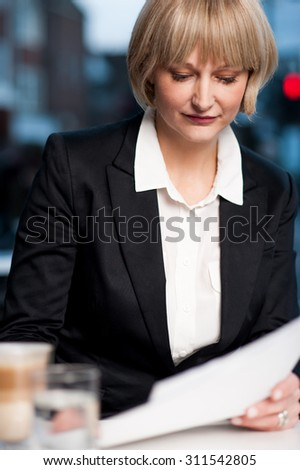 Business woman reviewing the report at cafe - stock photo