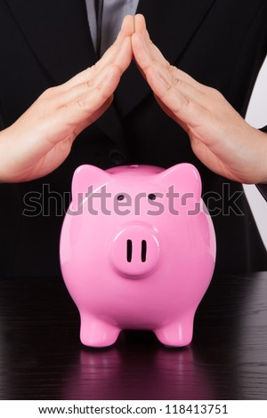 Business woman, roof shaped hands for estate, pink piggy bank. - stock photo