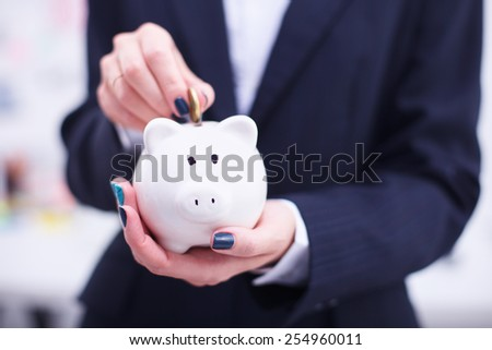 Business woman saving money in a piggybank