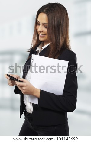 Business woman sending text message on mobile phone at office - stock photo