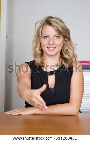 Business woman shaking hands at her desk  - stock photo