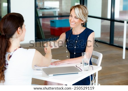 Business woman shaking hands with someone - stock photo