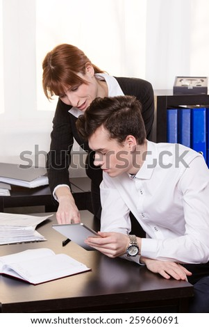 Business woman show something on the tablet and working together with colleagues.