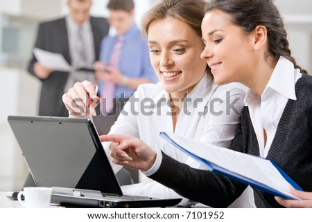 Business woman showing her working analysis to colleague and pointing to the monitor of laptop