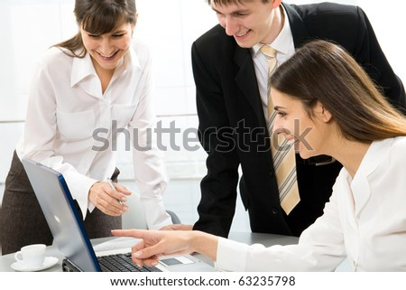 Business woman showing something on laptop to his colleagues - stock photo